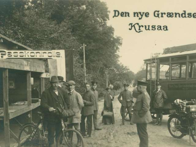 På billedet ses herrer, enkelt dame, de står til højre for en åben bod med skiltet Passkontrolle foroven. Til højre en bus fra Nord-Auto Überlandverkehrszentrale. Foran på kortet står: Den nye Grændse Krusaa
