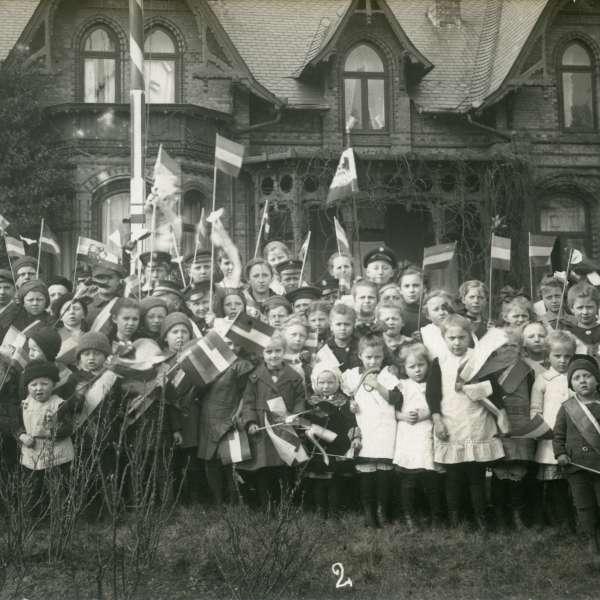 Stor forsamling af børn med det tyske flag i hånden foran en bygning i Kobbermølle. Nr. fire fra venstre i første række har to små Dannebrogssplitflag på brystet.